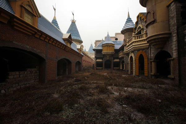 Weeds clog the street in China's abandoned fake Disneyland, 14 December 2011. David Gray / Reuters