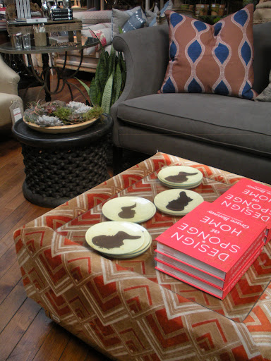 Silhouette dishes and a great read decorate this catchy ottoman.