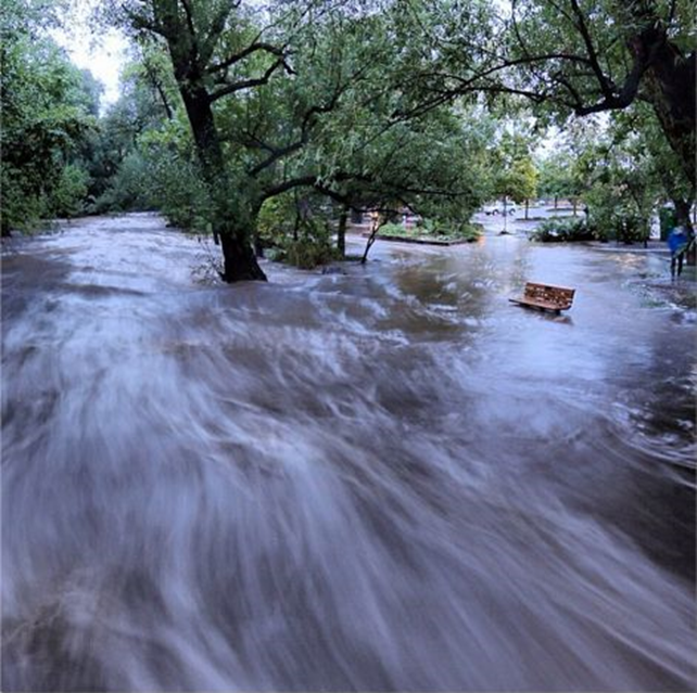 In this image made with a slow shutter speed which blurred the rushing water, flood waters course through a small park in Boulder, Colorado, Thursday morning, 12 September 2013. Heavy rains and scarring from recent wildfires sent walls of water crashing down mountainsides in the area. Photo: Jud Valeski