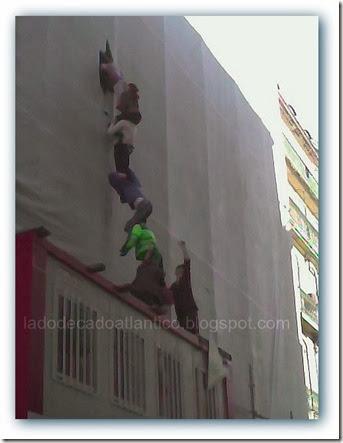 Imagem de uma coluna de manequins realistas imitando pessoas a subir num prédio em obras