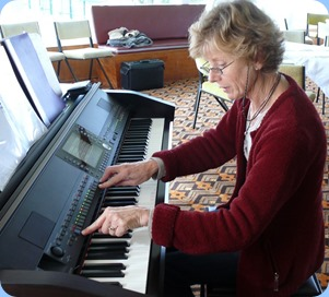 Denise Gunson taking advantage of Coffee Day to familiarize with the Clavinova ready for her Concert for the Club in September. Photo courtesy of Dennis Lyons.