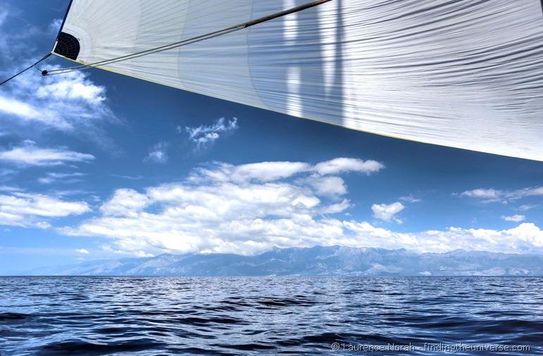 Blaues Segel vor Bergen hinter Wolken, Adria