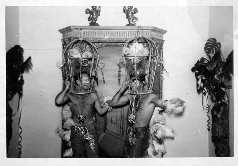 "Two men wear bird cages at a Henry Wooton Grace ""Japanese"" party thrown at his home. Grace was a Hollywood set designer and art director from 1935-1970. Circa 1951-1958."
