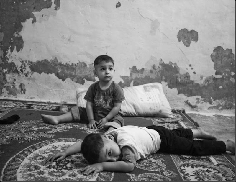 Qais (front) and his brother Laith, inside their one-room house in Amman. Qais and Laith live with their mother and grandmother, their father is missing in Syria. (Moises Saman/Magnum Photos for Save the Children)