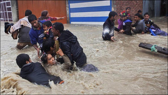 Kashmiri residents struggling to withstand sudden and strong water currents while wading through floodwaters in their efforts to move to safer places in Srinagar, India, 4 September 2014. Photo: Dar Yasin / AP Photo