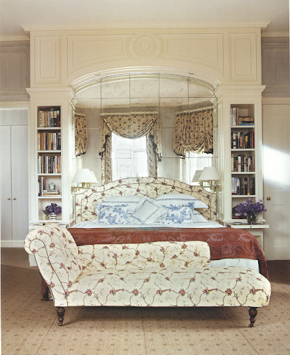 The bed in this European-traditional room is nestled in an alcove.