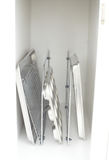 I use easily installed metal dividers to keep flat items organized vertically.