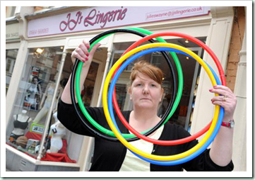 656160-4 : ©Lionel Heap : Melton News : JJ Lingerie in Melton Mowbray Ordered to Remove Olympic Rings Shop Window Display : Owner of JJ Lingerie Julie Swayne with the rings she has been ordered to remove from her shop window by trading standards.