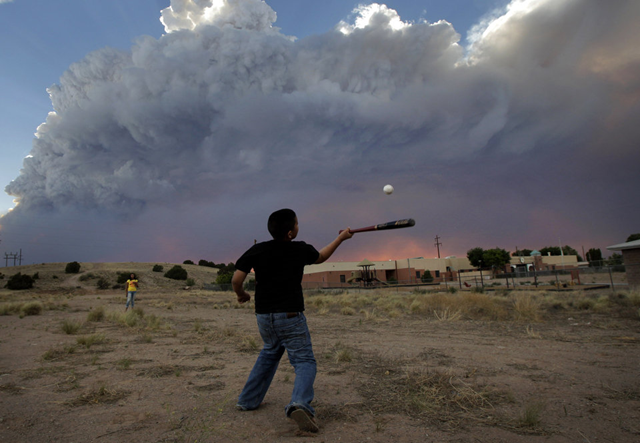 Alex Lopez, center, plays baseball with his sister Sugey while smoke generated by the Las Conchas fire covers the sky in Espanola, N.M., Wednesday, June 29, 2011. As crews fight to keep the wildfire from reaching the country's premier nuclear-weapons laboratory and the surrounding community, scientists are busy sampling the air for chemicals and radiological materials. AP Photo / Jae C. Hong