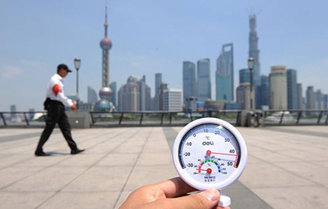 A security guard is on duty in the scorching sun along the Bund as a thermometer displays the temperature reaching 42 degrees Celsius in Shanghai, China, 6 August 2013. Photo: Imaginechina via AP Images