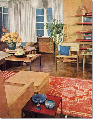 Emphasizing low long horizontal lines, this room achieves a sense of being bigger than it is. Long couch is three separate bed-length sections. Round walnut-top table is supported by an adjustable central pedestal. Featured in the December 1961 issue.