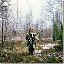 maria-ivanova-seen-here-in-traditional-evenk-dress-is-holding-a-rifle-used-for-practice-shooting-in-the-forest-after-a-family-picnic-in-zhigansk-the-evenk-people-are-a