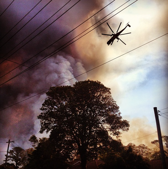 A helicopter flies over a fire front in the Blue Mountains of New South Wales, 19 October 2013. Photo: raddlegrams / Instagram