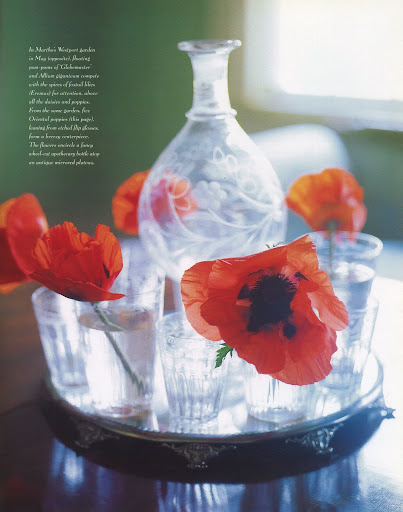 Five Oriental poppies, leaning from etched flip glasses, form a breezy centerpiece. The flowers encircle a fancy wheel-cut apothecary bottle atop an antique mirror plateau. (The Best of Martha Stewart Living -- Arranging Flowers)