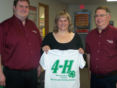 Terry Engelken and Jamie Collier of Federation Bank present club shirts to Riverside Enterprisers leader, Ann Lampe.  Photo Courtesy:  Washington County Extension.