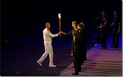 seven torchbearers ignite tiny single flames, showing the power of unity.
