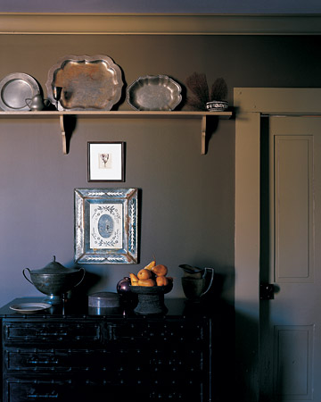 The silver pieces and Venetian mirrored frame pair gracefully with the dark wall. (marthastewart.com)