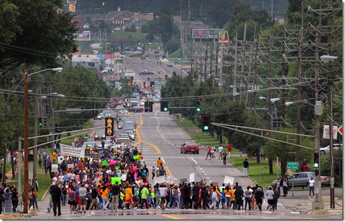 Marchers march up West Florissant Avenue, making a loop from the QuikTrip station to Highmont Road on Saturday, Aug. 16, 2014.  