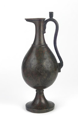 Ewer | Origin:  Iran | Period: 9th-10th century  Abbasid period | Details:  Vibrant metalworking industries in gold, silver, iron, and copper thrived in Basra. Craftsmen there specialized in manufacturing locks, mirrors, and other utensils. This pear-shaped vessel is similar to a bronze ewer that was made in Basra and is now in the Tiblisi Museum in Georgia, near Russia. The inscription around the neck of the Tiblisi ewer gives the craftsman's name and Basra as its place of manufacture. | Type: Brass | Size: H: 16.5  W: 43.7  cm | Museum Code: F1945.13 | Photograph and description taken from Freer and the Sackler (Smithsonian) Museums.