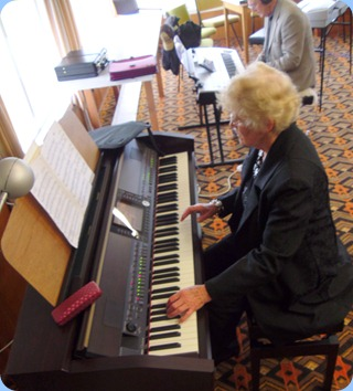 Ngaire McRae playing the Club's Clavinova whilst Len Hancy studies the layout of the Yamaha Tyros