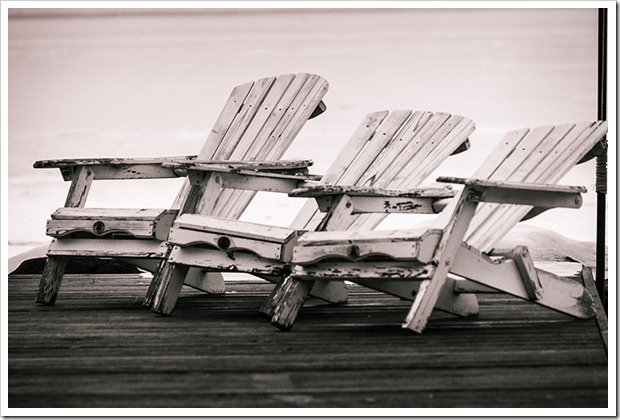 three white muskoka chairs on Lake Simcoe