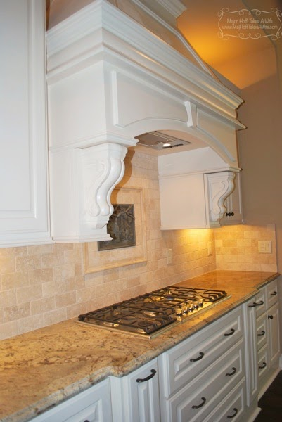 Gorgeous corbel arched kitchen vent above stovetop