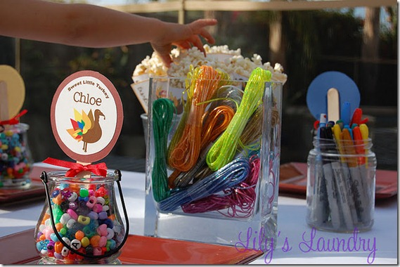 Thanksgiving kids table decorating and activity ideas--jars with beads and twine to make jewelry and crafts, paper cones filled with popcorn