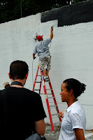 DCCAH Executive Director Gloria Nauden interviews with the Washington Post as Leon Rainbow paints the mural.
