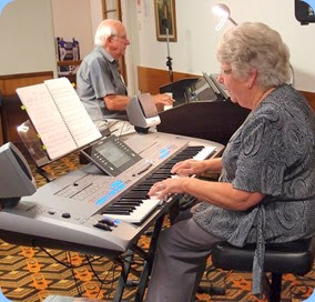 Barbara and Rob Powell played some solo pieces and some duets. Here they are duetting with Barbara playing their lovely Yamaha Tyros 5 (76 note version) and Rob on our Clavinova. Photo courtesy of Dennis Lyons.