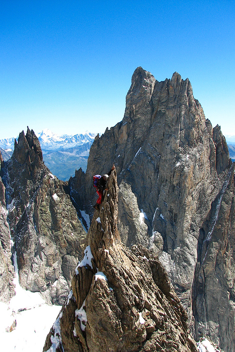 A guide balances on the sharp ridge before Punta Inomminata, Mont Blanc, Italy.