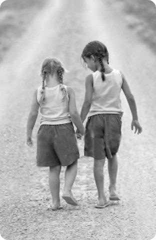 niñas amigas caminando una misma senda de la mano