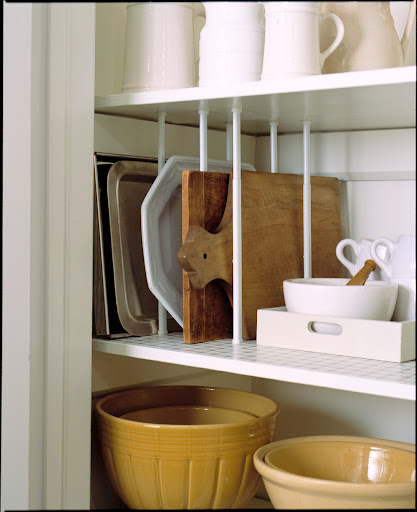 Curtain tensions rods fitted in between shelves in a pantry create vertical storage for platters, trays and cutting boards.