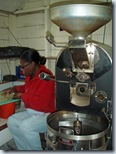 Pamsy sorts beans with coffee roaster to her left