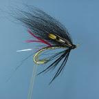 Silver Butcher Hairy V. (Ta jeszcze nie sprawdzona. Może pokażę ją naszym letnim trociom, może w przyszłym sezonie wypróbuję na którejś ze skandynawskich rzek). Haczyk – łososiowy podwójny, złoty  Tułów – koncówka ze srebrnej owalnej lamety, płaska srebrna przewinieta złotą owalną  Jeżynka – czarna o długich promieniach  Skrzydełka - sierść z ogona czarnego lisa polarnego z dodatkiem niebieskiego i granatowego Flashabou Ramiona – Jungle Cock