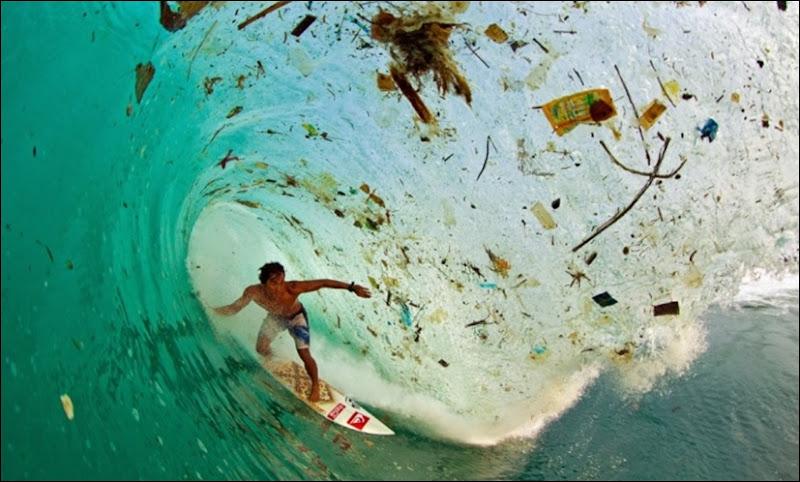 Indonesian surfer Dede Surinaya onda com lixo na ilha de Java