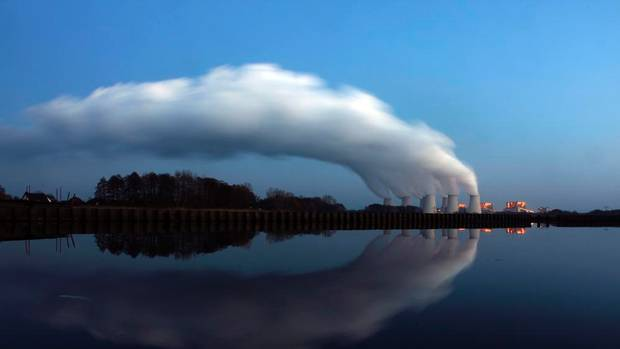 Steam billowing from the cooling towers of Vattenfall's Jaenschwalde brown coal power station is reflected in the water of a lake near Cottbus, eastern Germany, in this file picture taken in December 2009. PAWEL KOPCZYNSKI / REUTERS