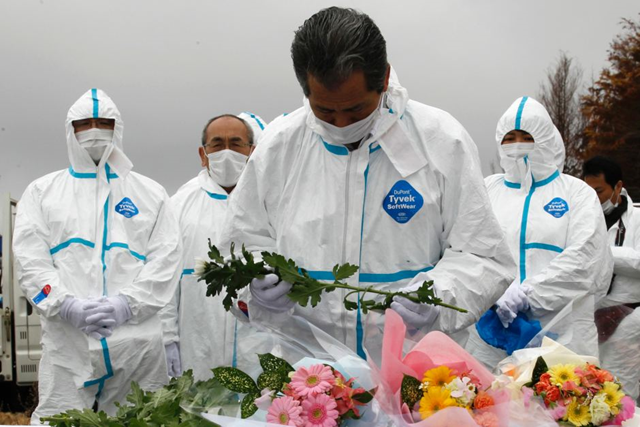 Evacuees in protective suits remember Fukushima disaster, during a Fukushima memorial service in 2012. Photo: Kim Kyung-hoon / Reuters