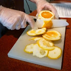 To properly slice an orange, you cut the skin and pith from the top and bottom first. Then from the sides, allowing your knife to follow the curve of the orange.