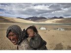 A Tibetan nomadic mother holds her baby outside their tent, on the high altitude mountainous terrain of Ladakh, India, near the Chinese-Tibetan border. <em>© Paula Bronstein</em>