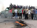 Un véhicule de Fardc passe avec des éléments de la PNC devant des partisans de l'UDPS  le 26/11/2011 le long du boulevard Lumumba à Kinshasa, lors de l'arrivé d'Etienne Tshisekedi en provenance du Bas-Congo. Radio okapi/ Ph. John Bompengo