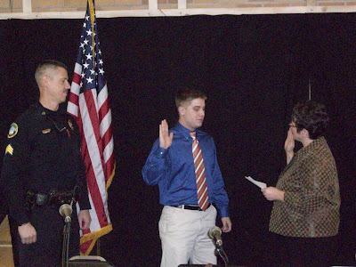 Mayor Sandra Johnson swearing in Brett Johnson as police officer at the November 16, 2011 City Council meeting.  Looking on is Officer Shawn Ellingson.