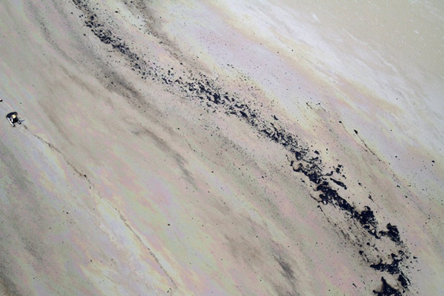 Aerial view of the tailings pond at the Athabasca tar sands mines, 18 May 2012. Most ponds are coated in a sheen of oil that can be deadly to waterfowl, like ducks and geese, that land on its surface. businessinsider.com