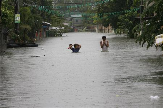 Children cross floodwaters at a submerged main street in Calumpit town, Bulacan province, north of Manila, 9 August 2012. Romeo Ranoco / Reuters