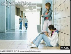 two_high_school_girls_by_lockers_watching_teen_boys_approaching_FAA011000013