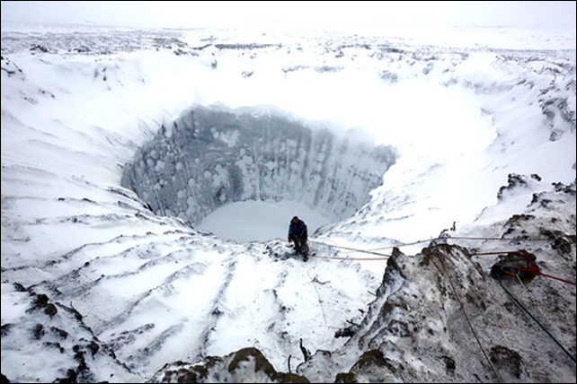Scientists from the Russian Centre of Arctic Exploration descend into a large crater on the Yamal Peninsula in northern Siberia, in November 2014. Photo: Vladimir Pushkarev / Russian Centre of Arctic Exploration