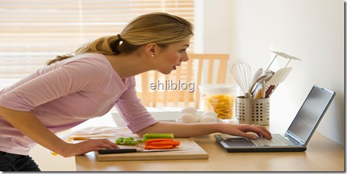 female cooking and looking at laptop in kitchen