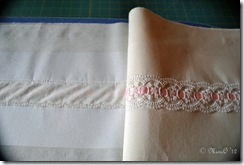 The flounce with the insertion lace sewn on, showing the tear-away stabilizer ironed onto the wrong side of the fabric.