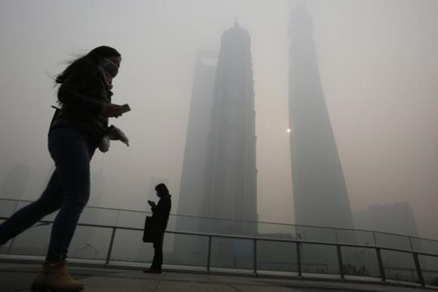 Residents wearing face masks use their mobile phones on a pedestrian overpass on a hazy day at the Pudong financial area in Shanghai, 6 December 2013. Photo: Aly Song / Reuters