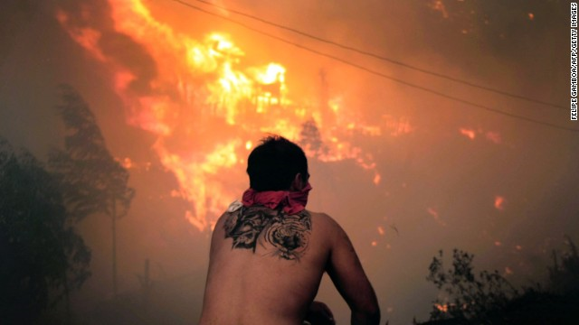 A man watches fires burn out of control in Valparaiso on Saturday, 12 April 2014. 'It's been one of the worst fires in history,' said Fernando Reseio, the fire superintendent in Vina del Mar. The fires were worsened by heavy winds and unusually high temperatures in the zone for this time of year, the Southern Hemisphere's autumn. Photo: Felipe Gamboa / AFP / Getty Images