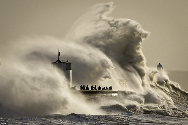 People photograph enormous waves as they break on Porthcawl, South Wales, where very strong winds and high seas from Winter Storm Hercules create dangerous conditions on 6 January 2014. Thrill-seekers were still risking their lives to storm-watch, defying guidance from police and the Environment Agency to stay away from dangerous coastlines. Photo: PA / Daily Mail